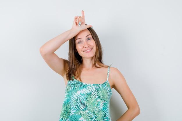 Giovane donna che mostra il segno del perdente sulla fronte e sembra allegra, vista frontale.