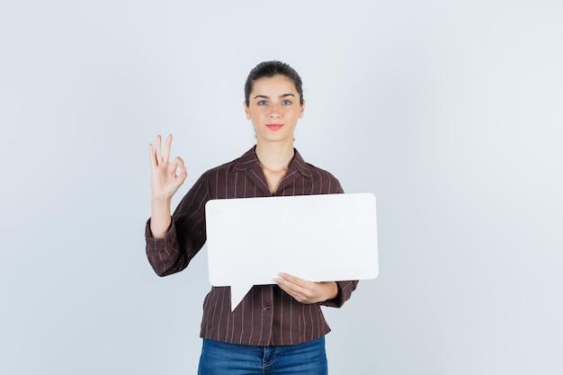 Giovane donna che mostra un gesto ok, tiene un poster di carta in camicia, jeans e sembra soddisfatta, vista frontale.