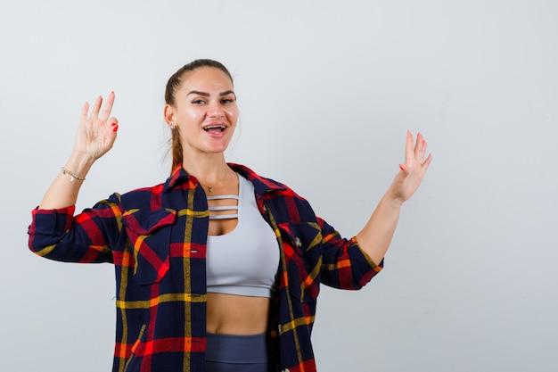 Giovane donna che mostra il segno ok in alto, camicia a quadri e sembra allegra, vista frontale.