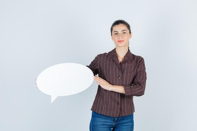 Giovane signora che mostra poster di carta in camicia, jeans e guardando fiducioso, vista frontale.