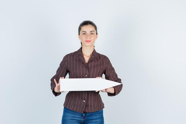 Giovane donna che mostra poster di carta in camicia, jeans e sembra carina, vista frontale.