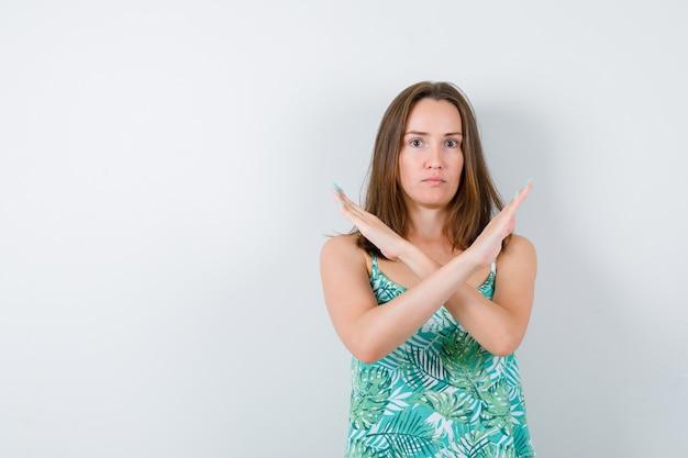 Giovane signora che mostra gesto di rifiuto e sembra seria. vista frontale.