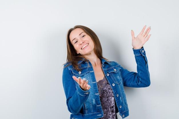 Giovane donna che mostra il segno di taglia in camicetta, giacca di jeans e sembra allegra, vista frontale.