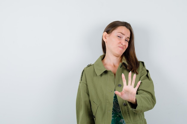 Giovane donna che mostra il gesto di arresto in giacca verde e sembra dispiaciuta, vista frontale.