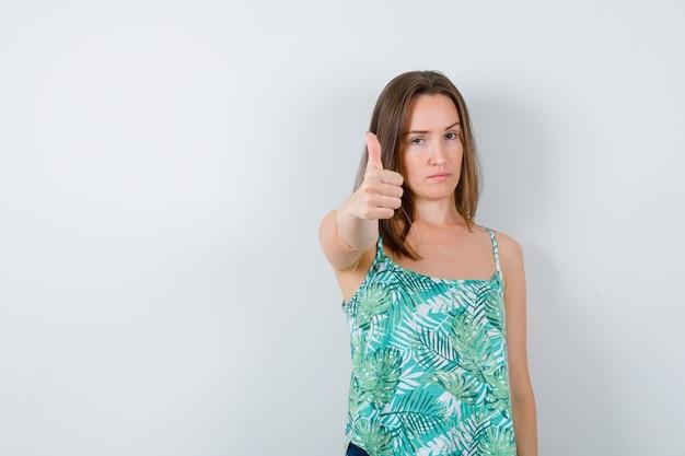 Giovane donna che mostra pollice in su e sembra seria, vista frontale.