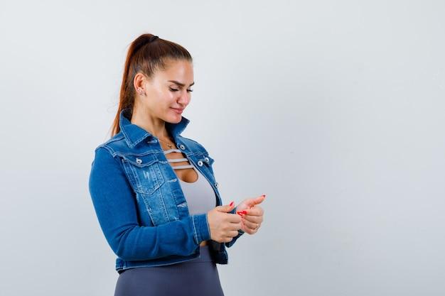 Giovane donna che mostra i pollici in alto, giacca di jeans e sembra soddisfatta, vista frontale.