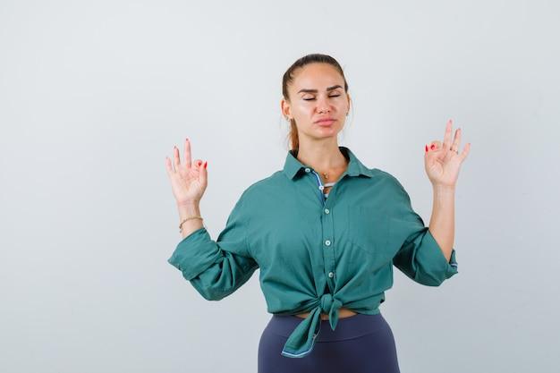 Giovane signora che mostra gesto di yoga con gli occhi chiusi in camicia verde e sembra rilassata. vista frontale.