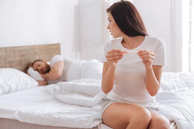 Giovane donna seduta su un letto e portando il suo test di gravidanza positivo in deliberazione mentre il suo ragazzo dorme dietro