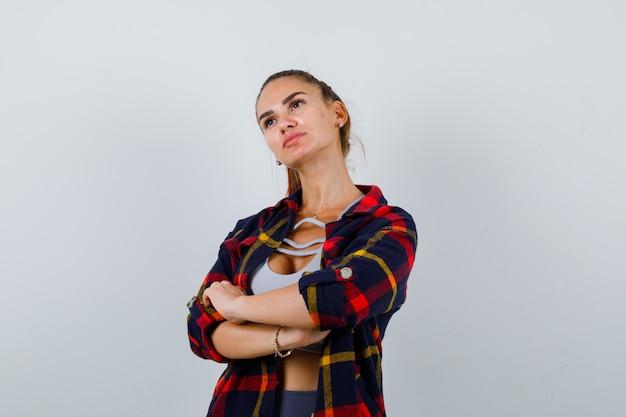 Giovane donna in piedi con le braccia incrociate in alto, camicia a quadri e sguardo pensieroso, vista frontale.