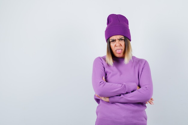 Giovane donna in piedi con le braccia incrociate mentre tira fuori la lingua in maglione viola, berretto e sembra risentita. vista frontale.