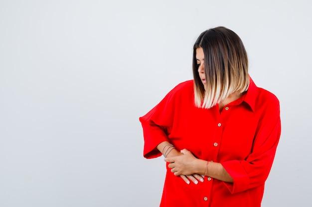 Giovane donna che soffre di dolore al fegato in camicia rossa oversize e sembra malsana, vista frontale.