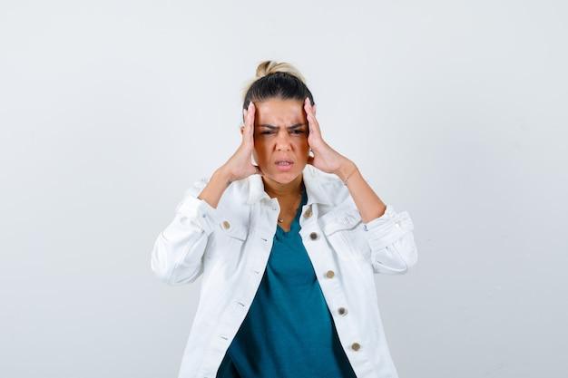 Giovane donna che soffre di forte mal di testa in giacca bianca e sembra infastidita, vista frontale.