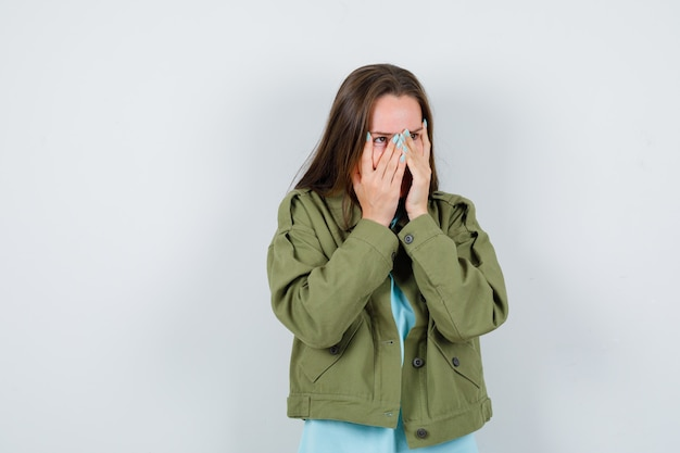 Giovane donna in t-shirt, giacca che guarda attraverso le dita e sembra carina, vista frontale.