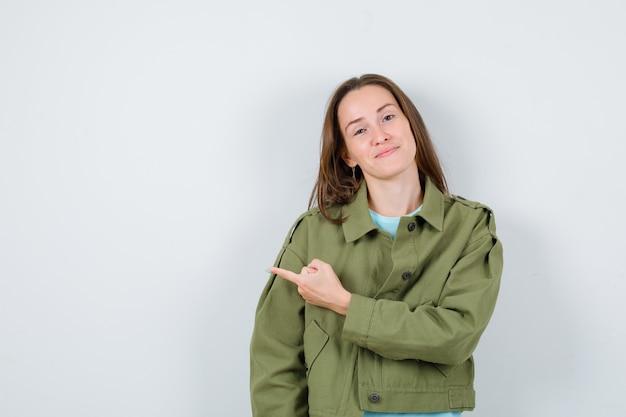 Giovane donna in t-shirt, giacca che punta verso il lato sinistro e sembra allegra, vista frontale.