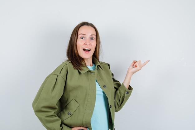 Giovane donna in t-shirt, giacca che punta verso il lato destro e sembra stupita, vista frontale.