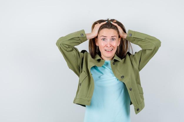 Giovane donna in t-shirt, giacca con le mani sulla testa e sguardo smemorato, vista frontale.