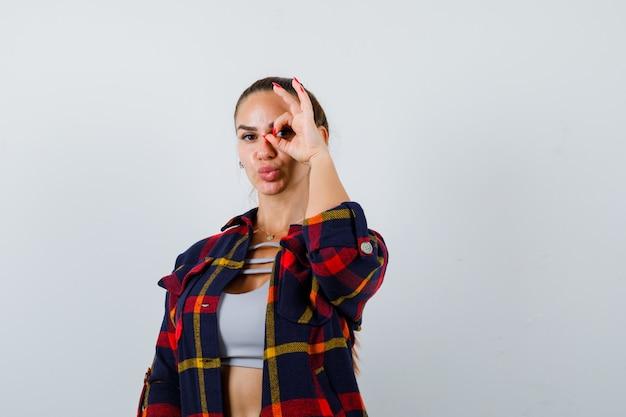 Giovane donna in cima, camicia a quadri che mostra il segno ok sull'occhio e sembra divertente, vista frontale.