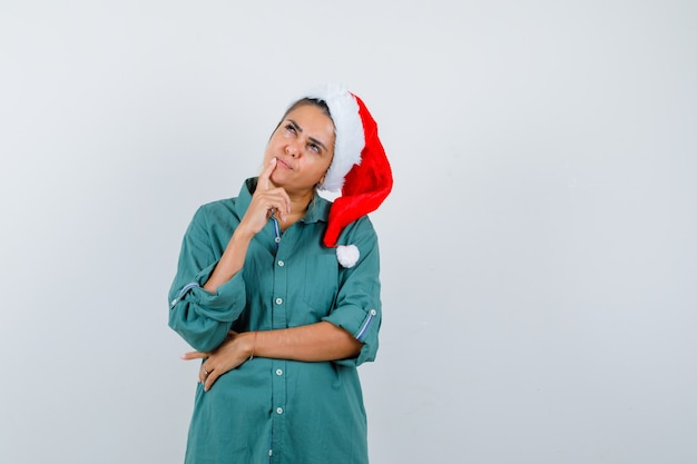 Giovane donna che tocca il dito vicino alla bocca con cappello di natale, camicia e sguardo pensieroso, vista frontale.