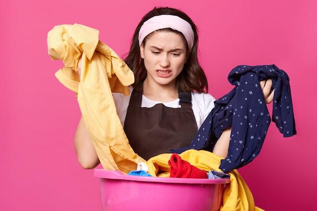 Giovane donna che indossa la fascia bianca e maglietta, grembiule marrone, con spiacevole espressione facciale, che ordina i vestiti sporchi