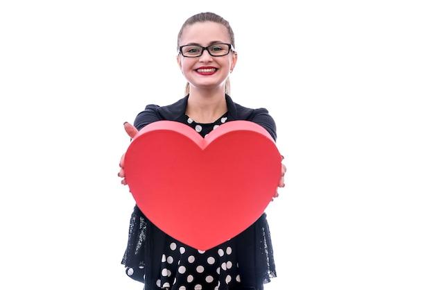 Giovane donna con un grande cuore rosso isolato su bianco