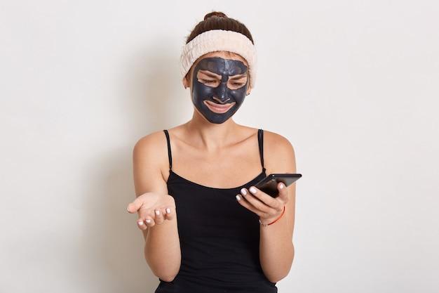 Giovane donna con maschera cosmetica facciale nera tramite cellulare
