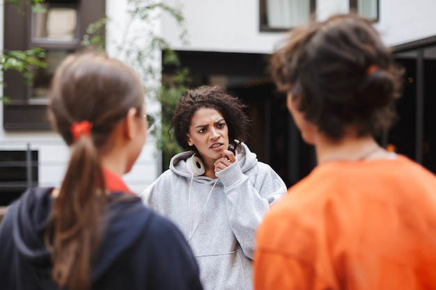 Giovane donna con i capelli ricci scuri in cuffie in piedi e guardando minuziosamente la sua amica mentre trascorreva del tempo con gli studenti nel cortile dell'università