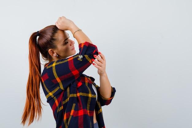 Giovane donna con pugno sulla fronte in alto, camicia a quadri e sguardo stanco, vista frontale.