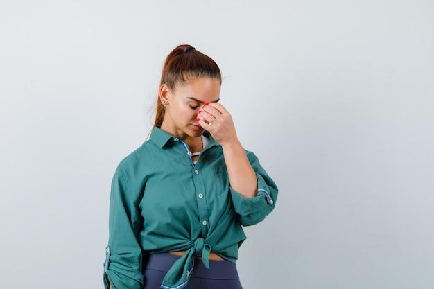Giovane donna con la mano sul viso, guardando in basso in camicia, pantaloni e guardando perplesso, vista frontale.