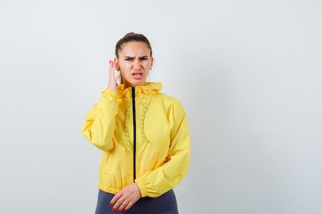 Giovane donna con la mano vicino al viso in giacca gialla e sembra infastidita. vista frontale.