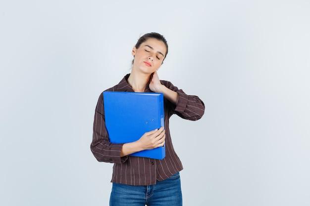 Giovane donna con la mano sul collo in camicia, jeans e sguardo doloroso, vista frontale.