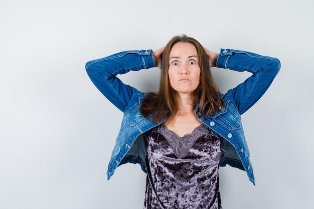 Giovane donna con le mani dietro la testa in camicetta, giacca di jeans e sguardo smemorato, vista frontale.