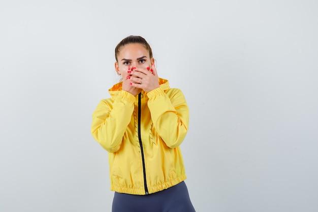 Giovane donna con le mani sulla bocca in giacca gialla e guardando perplesso, vista frontale.