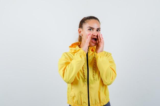 Giovane donna con le mani vicino alla bocca per dire il segreto in giacca gialla e sembra eccitata, vista frontale.