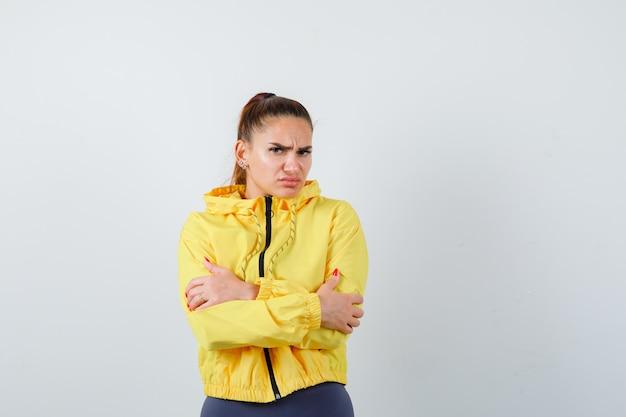 Giovane donna in giacca gialla che si abbraccia e sembra insoddisfatta, vista frontale.