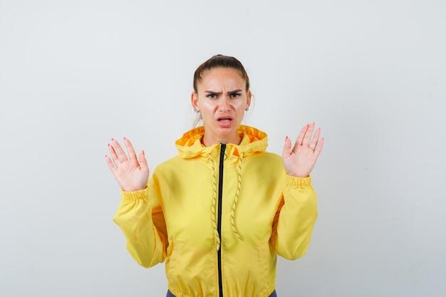 Giovane donna in giacca gialla che tiene le mani in gesto di resa e sembra ansiosa, vista frontale.