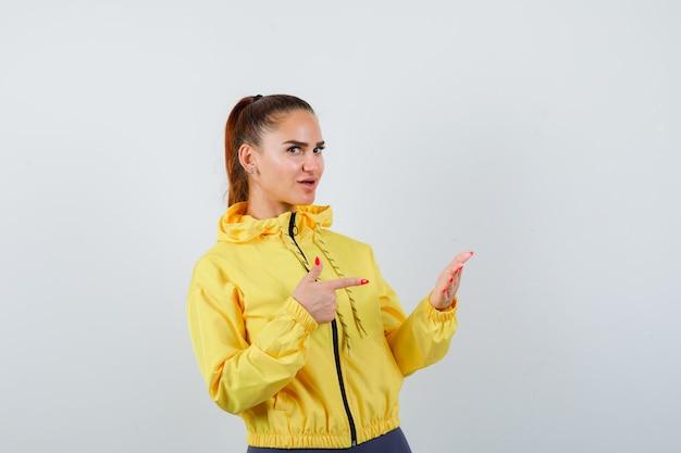 Giovane donna in giacca gialla che punta al palmo e sembra fiduciosa, vista frontale.