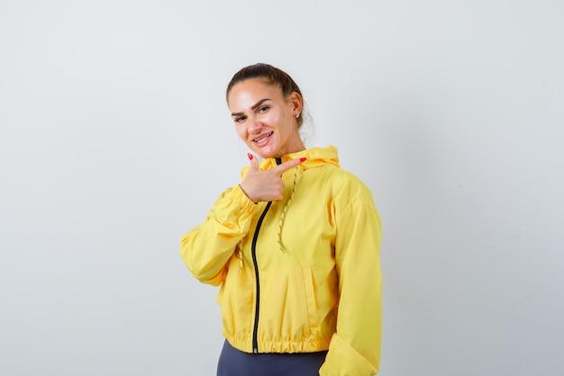 Giovane donna in giacca gialla che punta verso il lato destro e sembra allegra, vista frontale.