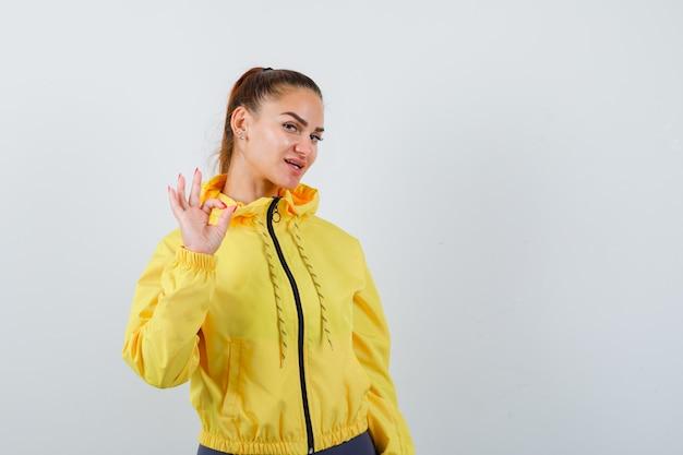Giovane donna in giacca gialla che mostra gesto ok e sembra sicura, vista frontale.