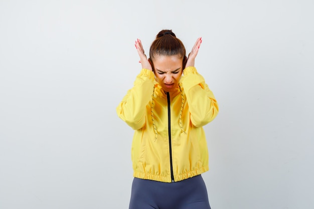 Giovane donna in giacca gialla con le mani sulle orecchie e dall'aspetto stressato, vista frontale.