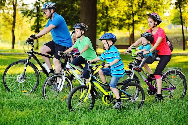 Giovane famiglia numerosa in bicicletta nel parco contro la superficie del verde e degli alberi