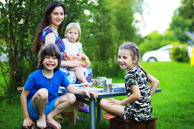 Una giovane famiglia numerosa a un picnic in una mattina d'estate. una bella mamma con bambini sta facendo colazione nel parco.