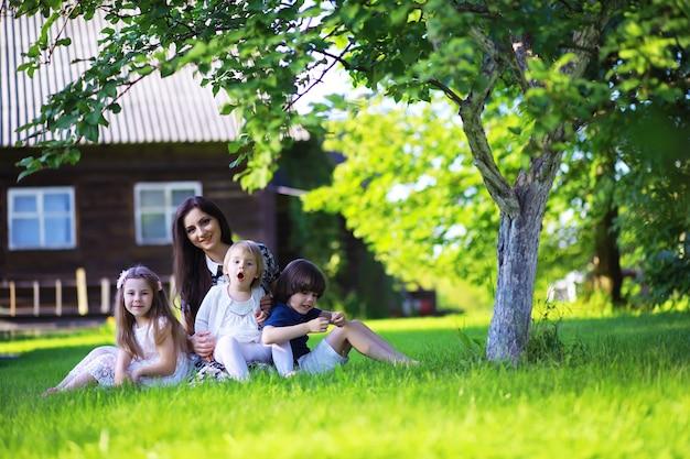 Giovane famiglia numerosa in una passeggiata mattutina estiva. la bella madre con i bambini sta giocando nel parco.