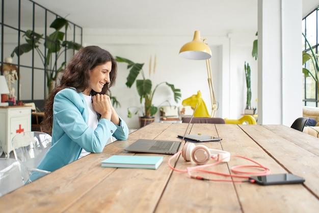 Giovane imprenditrice latinoamericana in una riunione online utilizzando un computer portatile impiegato femminile in video...