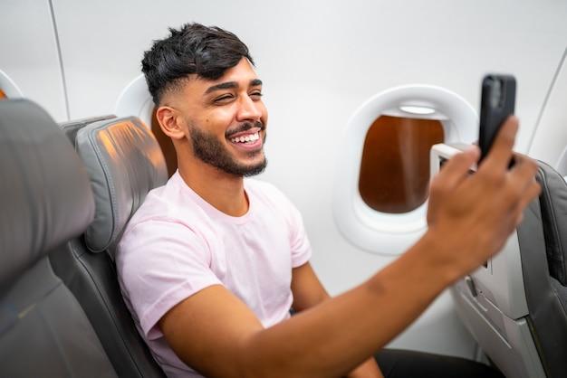 Giovane uomo latino-americano sorridente che fa una videochiamata sul suo telefono cellulare, seduto sull'aereo vicino al finestrino