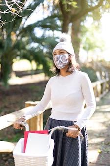 Giovane donna latinoamericana che cammina con la sua bicicletta