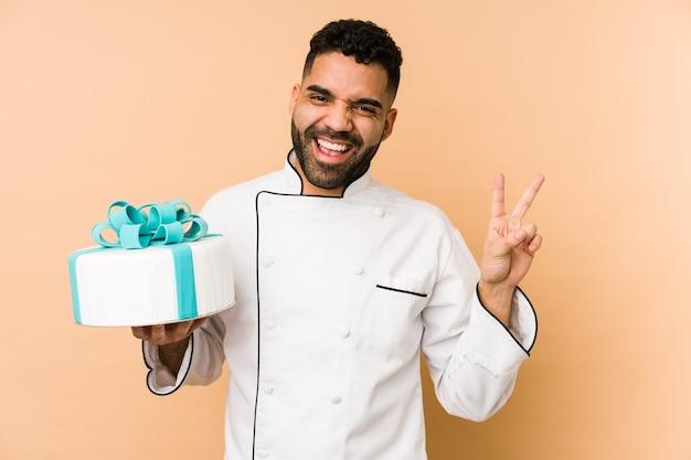 Giovane uomo panettiere latino che tiene una torta isolata gioiosa e spensierata che mostra un simbolo di pace con le dita.