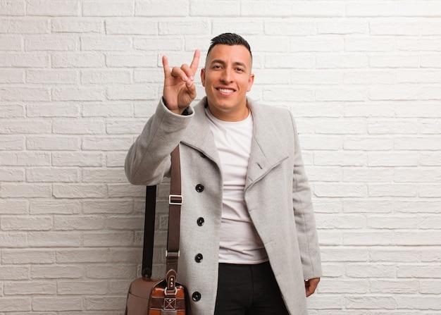Giovane uomo d'affari latino che fa un gesto di roccia