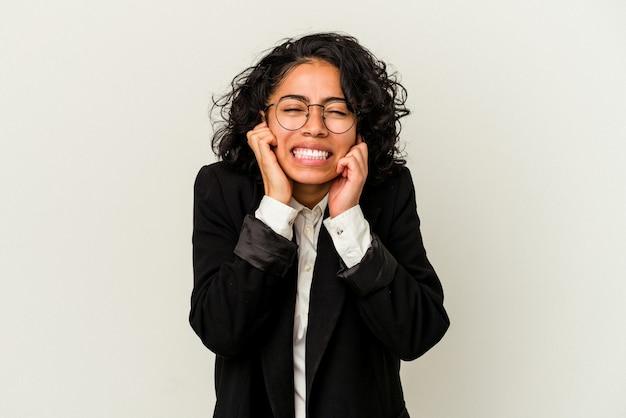 Giovane donna d'affari latina isolata su sfondo bianco che copre le orecchie con le mani.