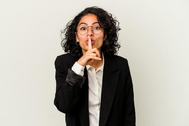 Giovane donna d'affari latina isolata su sfondo bianco mantenendo un segreto o chiedendo silenzio.