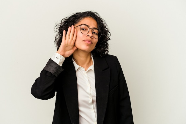 Giovane donna d'affari latina isolata su sfondo bianco cercando di ascoltare un pettegolezzo.